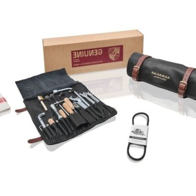 """Porsche Classic tool bag; suitable for all Porsche 356 A/B/C Carrera (1955 to 1965). Content: 5x double open-ended wrench (one each: 8x9, 10x11, 12x13, 14x15 and 17x19), 1x wheel nut wrench, 2x holding tools for V-belt, 1x combination pliers, 1x screwdriver, 1x Phillips screwdriver, 1x pull-off lever for hub cap, 1x flexible head socket wrench, 1x spark plug socket wrench, 1x hexagon socket wrench, 1x spark plug ratchet wrench, 1x stubby screwdriver, 1x brush, 1x feeler gauge, 1x wheel nut, 1x narrow V-belt, 2x spark plug holder, 1x cleaning cloth. While the original was made of synthetic leather, the impressive new edition of the tool bag for the 356 Carrera is finished in extremely high-quality leather. Just like the design for the remaining 356 models, this version also features brown leather straps for closing the tool bag. The Carrera engine has a dual ignition system, meaning it has two spark plugs per cylinder. For this reason, the developers of the new tool bag have also provided two slots for spark plugs. What's more, the tool bag is not just designed for the 356 Carrera – it can be used with all models driven by a """"Fuhrmann"""" engine, including the 550 Spyder, 718 or 904 racing cars. All of the tools have been manufactured in accordance with original drawings by the original supplier."""
